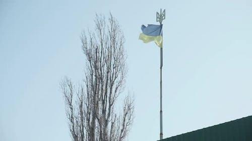 Schäbige blaue und gelbe ukrainische Flagge auf einem langen Pole mit einem Dreizack