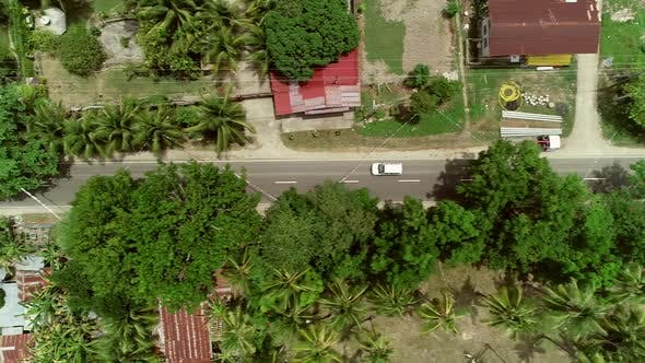 Aerial view following car on road in Batuan, Philippines.