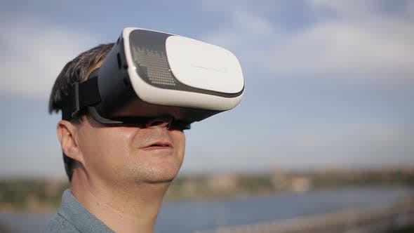 Man Uses a Virtual Reality Glasses on the Background of Blue Sky