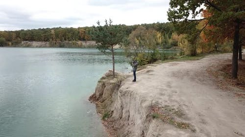 Man standing on shore. Aerial view of man standing on lake shore and taking photo of nature