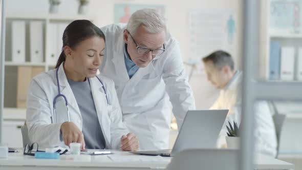Thumbnail for Senior Male Doctor Working on Laptop with Young Female Colleague