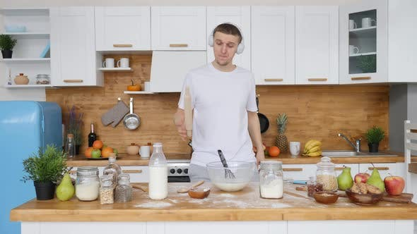 Thumbnail for Man Dancing In Headphones While Cooking Breakfast In Kitchen