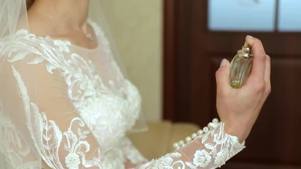 Close up. Girl sprays perfume. The bride on her wedding day.