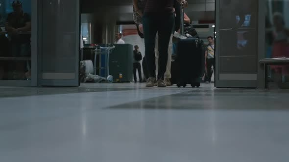 People with luggage coming out of the airport