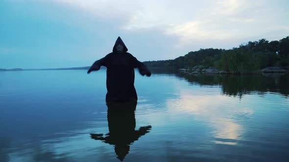 Scary figure in black mantle in the river