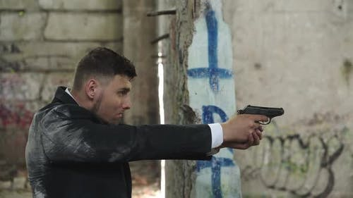 Man in Suit Shooting with Pistol in Abandoned Building