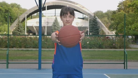 Porträt eines jungen Mädchens, das auf die Kamera schaut und einen Basketball nach vorne streckt. Ein Teenager in