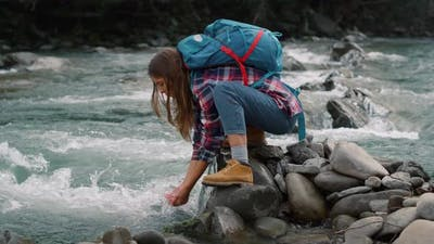 Tourist Touching Water in River