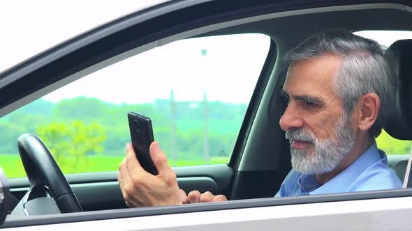 Thumbnail for Senior Man Sits in the Car and Works on the Smartphone - Closeup Shot From Side - Countryside