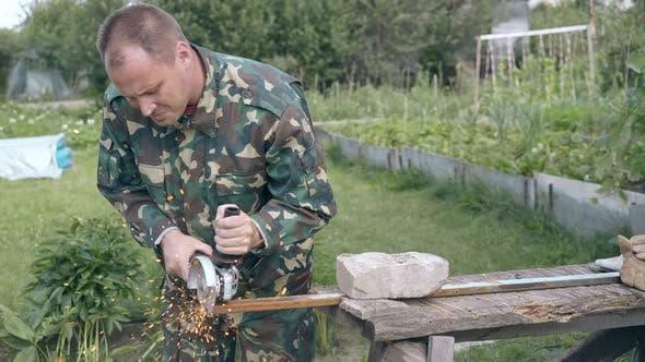 Thumbnail for Mature Man Cuts Metal Detail with Circular Saw in Garden