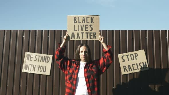 Poster BLACK LIVES MATTER in hands of woman. Stop Racism concept.