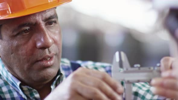 Thumbnail for Industrial Worker Taking Measurement with Caliper