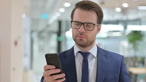 Thumbnail for Businessman Browsing Internet on Smartphone at Work