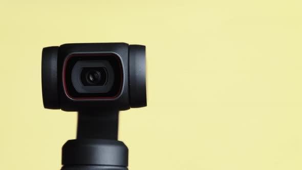 Mechanical Gimbal Camera Lens Rotates on Yellow Background Robotic Camera Macro