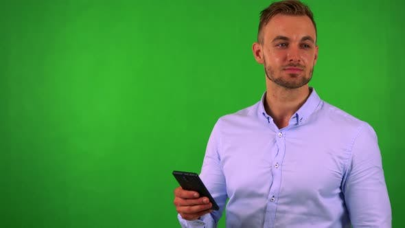 Thumbnail for Young Handsome Business Man Works (Typing) on Smartphone - Green Screen - Studio