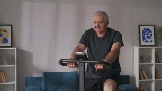Portrait of Middleaged Man on Stationary Bike in Apartment Training at Home Keeping Good Physical