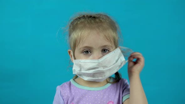 Cover Image for Little Girl Takes Off a Medical Mask on a Blue Background