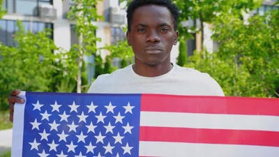 Camera Zoom in Afroamerican Man Holding an American Flag and Looks Camera
