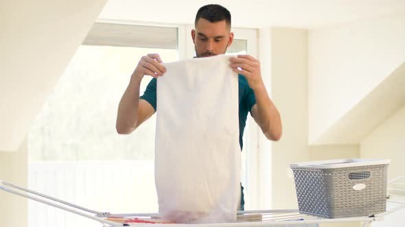 Thumbnail for Man Taking Laundry From Drying Rack at Home