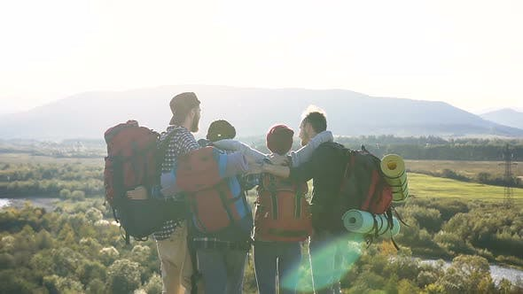 Four Caucasian Friends With Backpacks Rest in a Picturesque Place of Mountains at Sunset
