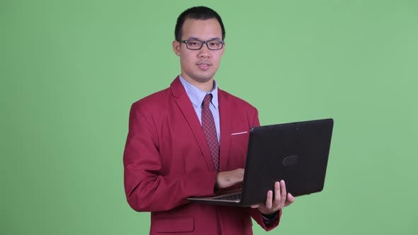 Cover Image for Happy Asian Businessman Talking While Using Laptop