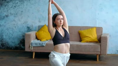 Woman in Her Living Room in Warrior Yoga Pose