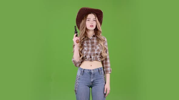 Thumbnail for Cowgirl Holds a Revolver in Her Hands and Aiming at the Villain. Green Screen