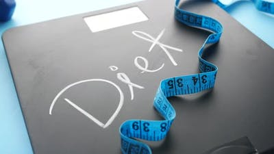 Diet Text on Weight Scale with Dumbbell and Measurement Tape on Blue
