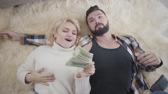 Thumbnail for Blond positive kaukasische Frau nimmt Geld von ihrem Mann und küsst ihn auf Wange. Reiche Ehegatten