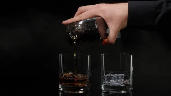 Barman Pouring Whiskey Cognac Brandy From Bottle Into Glasses with Ice Cubes on Black Background