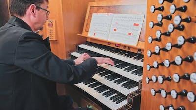 Organist Plays Music on Church Organ
