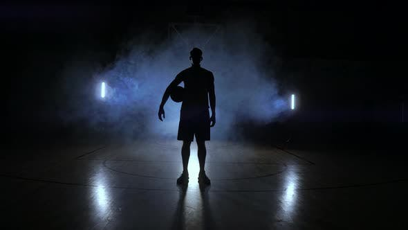 Cover Image for Basketball Player Knocks the Ball in the Light of the Lamps Shining Behind Stands in the Duma and