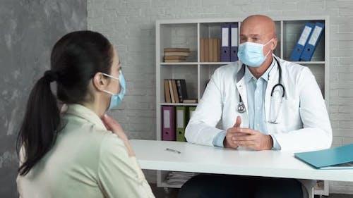 Reife Ärztin mit medizinischen Gesichtsmasken, Beratung von Patientin in einer Klinik. Frau palpiert Lymphe
