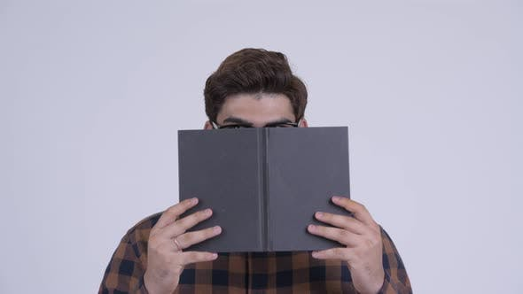 Cover Image for Young Indian Hipster Man Covering Face with Book