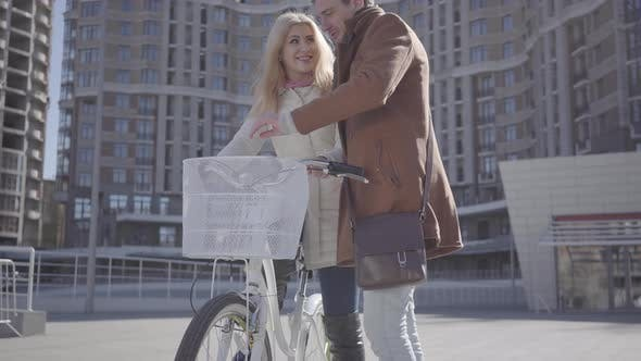 Thumbnail for Handsome Man in Brown Coat Teaching His Girlfriend To Ride the Bicycle in the City, Both People