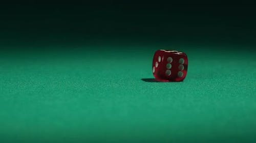 Closeup view of red casino dice rolling on green surface in slow-motion