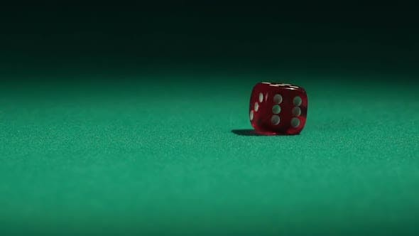 Thumbnail for Closeup view of red casino dice rolling on green surface in slow-motion