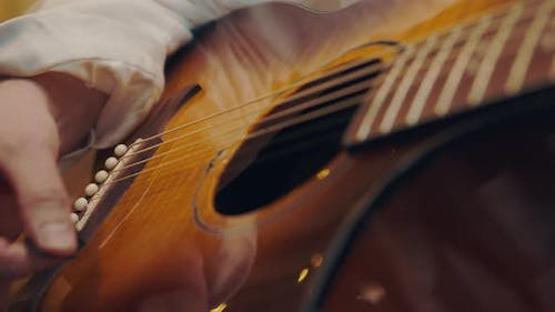 A Male Hand Plays the Guitar Close Up in Warm Light and Warm Tones