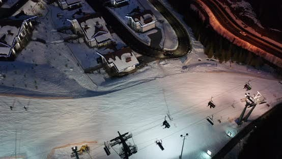 Thumbnail for Aerial View of Skiers Go Down Ski Slopes Near Ski Lifts on Ski Resort at Night.