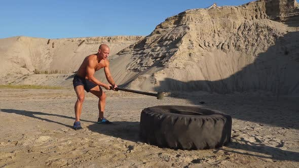 Cover Image for Bald Man Strongman Hits a Hammer on a Huge Wheel in the Sandy Mountains in Slow Motion