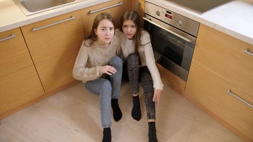 Two Girls Hiding From Aggression or Anger of Parent