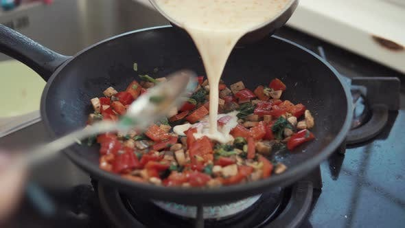 Thumbnail for Cook Is Pouring Scrambled Eggs in Pan with Frying Vegetables for Cooking Omelet