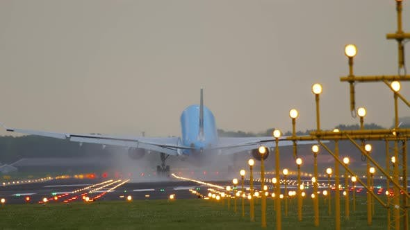 Rear View of Aircraft Touching and Braking Runway