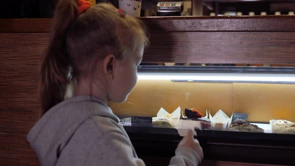 Small Fairhaired Girl with a Ponytail of Hair on Her Head Chooses a Dessert in the Window with