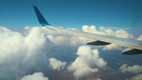 View of jet airplane wing from inside flying through white puffy clouds in blue sky. Travel