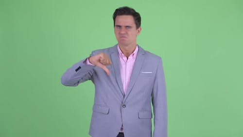 Angry Young Businessman Giving Thumbs Down
