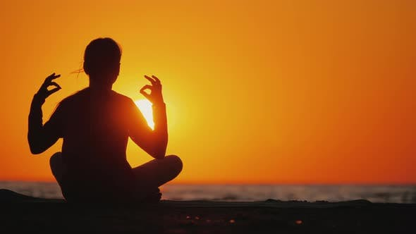 Cover Image for Young Girl Meditates in a Picturesque Place at Sunset