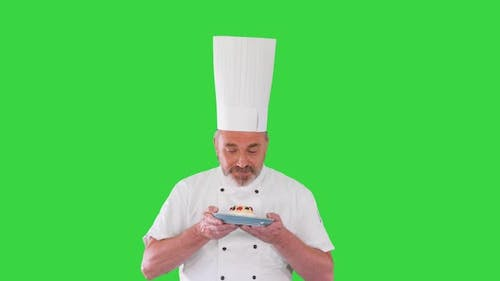 Happy Chef Looking at Camera Holding a Dessert on a Green Screen Chroma Key