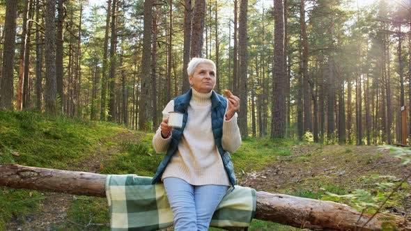 Seniorin Tee trinken und Kuchen essen im Wald