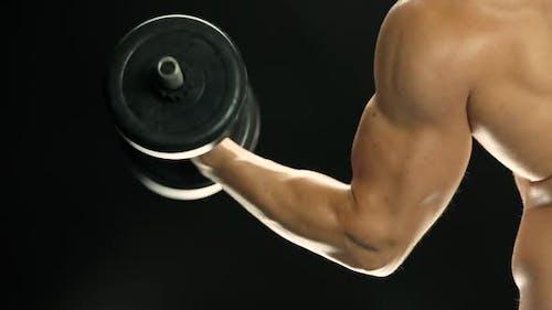 Muskulöser Mann macht Kurzhantel-Übungen.